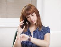谈话在电话和检查时间的女孩 免版税图库摄影