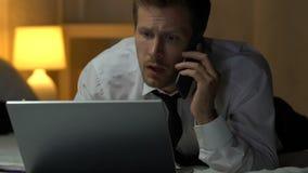 谈话在电话和研究膝上型计算机的企业人在床,多任务上 股票录像