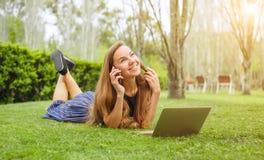 谈话在电话和研究膝上型计算机的女孩 库存图片
