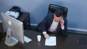谈话在电话和研究计算机的商人在办公室 免版税库存照片