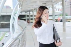 谈话在电话和走在走道的可爱的年轻亚裔秘书在城市 图库摄影