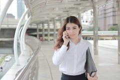 谈话在电话和走在走道的美丽的年轻亚裔女商人画象在城市 图库摄影