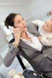谈话在电话和运载她的婴孩的繁忙的妇女 免版税图库摄影