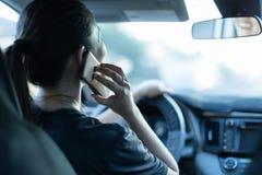 谈话在电话,当驾驶时 发短信和驾驶 在轮子后的分散的司机 库存图片
