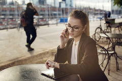 谈话在selfphone和看手表的女商人 图库摄影