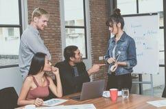 谈话小组亚裔和不同种族的商人和关于数字片剂的微笑和介绍信息在coworking 免版税图库摄影