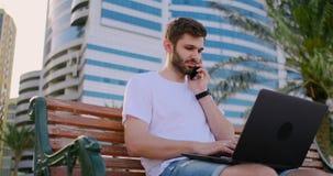 谈话年轻人在有棕榈树的公园和的膝上型计算机坐电话 股票录像