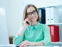 谈话年轻可爱的女商人画象坐在办公室椅子的玻璃的运作在台式计算机  免版税库存照片