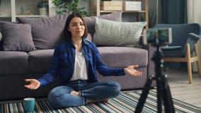 谈话年轻女人的vlogger在家打手势有智能手机的记录的录影 股票录像