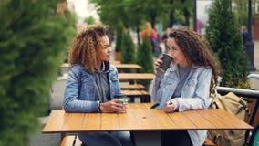 谈话快乐的少妇的最好的朋友笑和,当坐在室外咖啡馆和饮用的咖啡,女孩时的桌上 股票录像