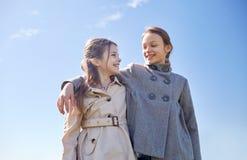 谈话愉快的小女孩拥抱和户外 免版税图库摄影