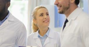 谈话愉快的微笑的科学家的队拿着与实验的结果的文件,成功的研究员队 股票视频
