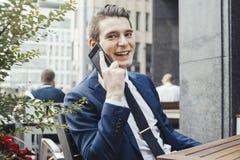 谈话由手机和看观察者的年轻可爱的商人 免版税库存照片