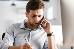 谈话由智能手机和写某事的严肃的商人 免版税库存图片