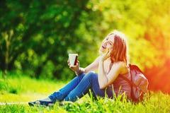 谈话由电话和拿着咖啡的可爱的少妇 免版税库存图片