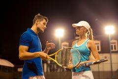 谈话男性和女性的网球员户外 库存照片