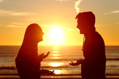 谈话的十几岁朋友或夫妇愉快在日落 免版税库存图片
