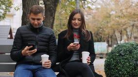 谈话的朋友浏览互联网,饮用的咖啡和,当坐一条长凳,在街道时 股票录像