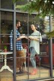 谈话的男人和的妇女,当喝咖啡时 图库摄影