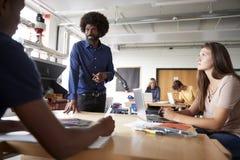 谈话的老师坐在设计和技术教训的工作台的编组高中生 免版税库存图片