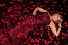 说谎一件红色的礼服的可爱的少妇支持与花 免版税库存图片