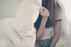 说谎与在床上的毯子的年轻亚裔妇女的幸福早晨 蓝色分行休息日霜谎言天空雪结构树冬天 复制空间 免版税图库摄影