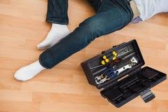 说谎与工具箱子的一个人的中间部分 免版税图库摄影