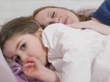 说谎与母亲的女孩在床上 免版税库存照片