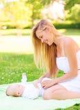 说谎与毯子的小婴孩的愉快的母亲 免版税库存照片