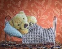 说谎与温度计的病的玩具熊在床家 免版税图库摄影