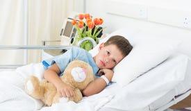 说谎与玩具熊的男孩在医院 图库摄影
