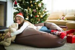 说谎与玩具熊的美丽的女孩 圣诞前夕礼品节假日许多装饰品 图库摄影