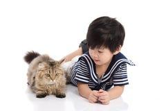 说谎与虎斑猫的逗人喜爱的亚裔孩子 免版税库存照片