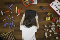 说谎和使用与片剂计算机的小男孩 全部在他附近的玩具在木地板上 顶视图 免版税库存图片