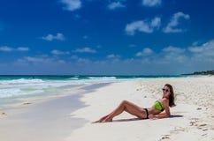 说谎和可及太阳的年轻逗人喜爱的妇女热带沙子海滩 库存照片