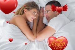 说谎和看彼此的逗人喜爱的夫妇的综合图象在床上 库存图片