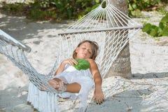 说谎和睡觉在吊床的疲乏的小女孩在庭院里 免版税图库摄影