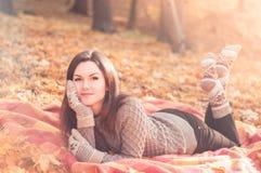 说谎在一个地毯的年轻美丽的妇女在秋天公园 免版税库存图片