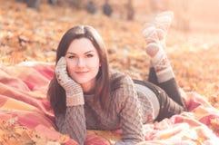 说谎在一个地毯的年轻美丽的妇女在秋天公园 免版税库存照片