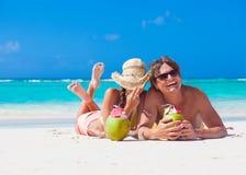 说谎在一个热带海滩在巴巴多斯和喝椰子鸡尾酒的愉快的年轻夫妇 免版税图库摄影
