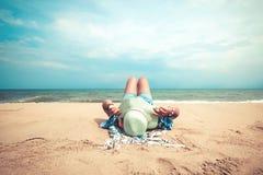 说谎在一个热带海滩的少妇,放松并且晒日光浴 库存图片