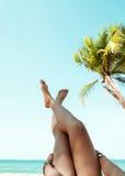 说谎在一个热带海滩的少妇,放松舒展被晒黑的苗条腿 免版税库存图片