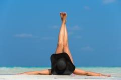 说谎在一个热带海滩的帽子的美丽的妇女 免版税库存图片