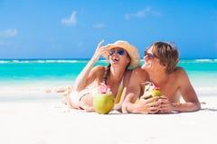 说谎在一个热带海滩的愉快的年轻夫妇  库存图片