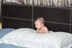 说谎在一个白色枕头的逗人喜爱的亚裔婴孩,在床上 库存照片