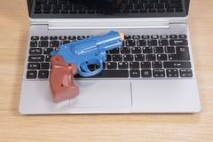 说谎在一台开放膝上型计算机的玩具枪 库存图片