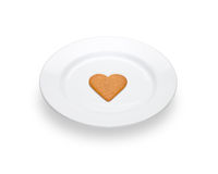说谎在一块白色板材的一姜饼心脏 免版税库存图片