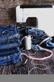 说谎在一张木桌上的堆牛仔裤 图库摄影