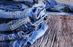 说谎在一张木桌上的堆牛仔裤 免版税库存照片
