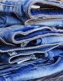 说谎在一张木桌上的堆牛仔裤 库存图片